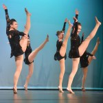 JV captains sophomore Maggie Mulligan and sophomore Gia Hense high kick during their dance. Photo by Katherine McGinness