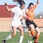 Freshmen Eleanor Hlobik fights over the ball against SMNW defender. Photo by Carson Holtgraves