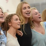 Singing along to the school song for their last assembly, seniors Emory Foster, Ellie Booton, Sophie Theide, and Ellie Mitchell lock arms, Photo by Morgan Plunkett