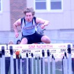 Sophomore Michael Perry competes in the 100 meter hurdle race. Photo by Maddie Smiley