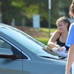 Freshman Ari Sharman smiles at the driver of a car as she dries it. Photo by Ally Griffith