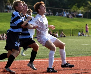 Waiting for a corner kick to drop into the box, senior Tommy Nelson pushes against sophomore Henry Harrison and junior Carson Jones. Photo by Lucy Morantz