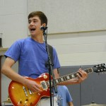 Senior Cal Knabe plays the electric guitar during the Orbiters performance at the Lancer Dancer Pancake Breakfast. Photo by Katherine McGinness