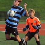 Sophomore Peter Kohring chest bumps the corner kick to keep the goalie, freshman Will Lowry, from stealing it. Photo by Izzy Zanone