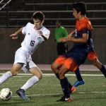 Junior Connor O'Toole cuts the ball past an Olathe East player. Photo by Audrey Kesler