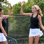 Freshman Quinci Cartmell and Allison Wilcox high five after a successful win against the opposing team. Photo by Audrey Kesler
