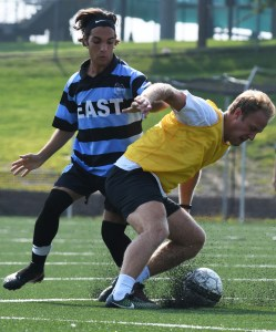 Senior Cooper McCullough attempts to take the ball away from the alumni player. Photo by Carson Holtgraves