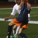 Senior Sam Thompson fights for the ball against Olathe East player. Photo by Izzy Zanone