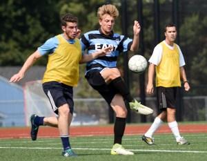 Senior Sam Thompson kick the ball away from his alumni opponent. Photo by Ellen Swanson