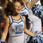 Senior Mya Hutcherson jumps with the cheerleaders leading the student section in a cheer. Photo by Izzy Zanone