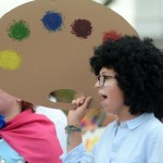 Freshman Olivia Olson holds up a cardboard paint palette while walking with the visual arts float. Photo by Kate Nixon