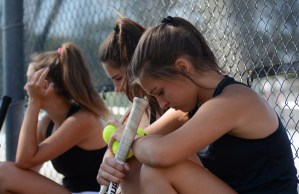 Sophomore Caroline Chisholm focusses as her teammates discuss strategy before the matches. Photo by Ty Browning