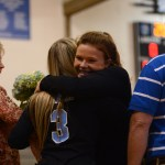 Junior Andie Mcconnell gives teammate Gracey Stoetzer a hug and hands her a bouquet of flowers. Photo by Aislinn Menke