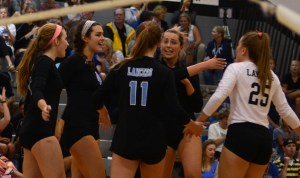 Junior Mallory Frank, Sophomore Brigid Wentz, Senior Victoria Yedo, and Senior Sydney Ashner high five and form a group huddle after scoring a point. Photo by Aislinn Menke