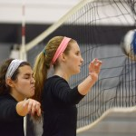 Brigid Wentz and Katie Aliber wait at the net, as their teammates hit the ball into the net. Photo by Luke Hoffman