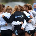 The girls varsity cross country team gets pumped up before their regionals race. Photo by Luke Hoffman
