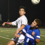 Junior Eren Eksinar heads the ball away from the Leavenworth defender. Photo by Ty Browning