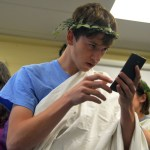 Senior George Sullivan checks his laurel wreath using his phone before the ceremony. Photo by Ally Griffith