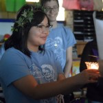 Junior Jia Self holds a candle while Junior Nat Nitsch recites a speech. Photo by Ally Griffith
