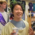 Sophomore Lily Turner holds up breadsticks as part of the Roman feast the officers set up after the ceremony. It also included other foods typically eaten in ancient Rome, such as pita bread and hummus. Photo by Ally Griffith