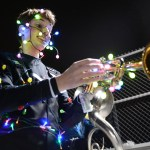 Sophomore Christopher Short wraps himself and his trumpet in lights for the glow show after the football game. Photo by Aislinn Menke