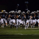 The varsity football team rushes onto the field at the start of the game. Photo by Audrey Kesler