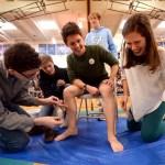 Senior Julia Stopperan cracks up as she rips off senior Denny Rice's leg hair with sophomore Ian Gould and junior Dane Erickson. Photo by Ellie Thoma