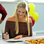 Senior Emma Linscott signs her commitment to swim at the University of Minnesota. Photo by Elizabeth Anderson