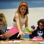 Senior Sidney Embry cleans up the paper scraps leftover from the other students. Photo by Grace Goldman