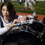 Junior Kira Schoke wraps lights around her drum in preparation for the glow show. Photo by Kate Nixon