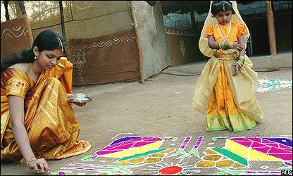 Joven y niña haciendo una pintura tradicional en India
