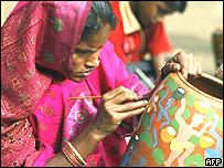 Joven india pintando un pote de cerámica