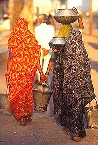 Mujeres indias cargan agua