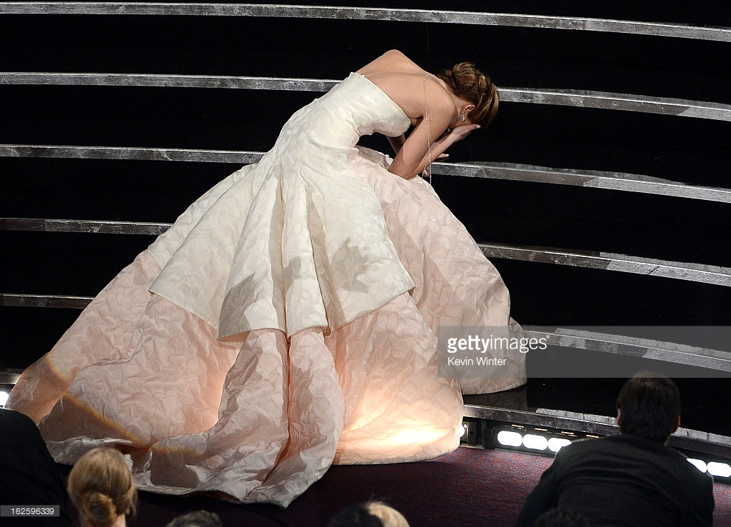 """HOLLYWOOD, CA - FEBRUARY 24:  Actress Jennifer Lawrence reacts after winning the Best Actress award for """"Silver Linings Playbook"""" during the Oscars held at the Dolby Theatre on February 24, 2013 in Hollywood, California.  (Photo by Kevin Winter/Getty Images)"""