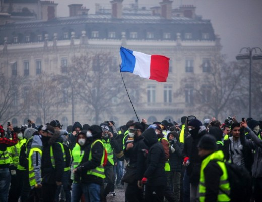 "Demonstrators gather near the Arc de Triomphe as a French flag floats during a protest of Yellow vests (Gilets jaunes) against rising oil prices and living costs, on December 1, 2018 in Paris. - Anti-government protesters torched dozens of cars and set fire to storefronts during daylong clashes with riot police across central Paris on December 1, as thousands took part in fresh ""yellow vest"" protests against high fuel taxes. (Photo by - / AFP)"