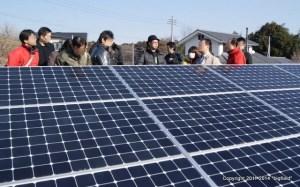太陽光発電パネルを前に説明を聞く見学会参加者の皆さん