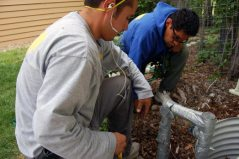 Dustin (left) and Joel run the grounding wire into -- you guessed it! -- the ground outside our house.