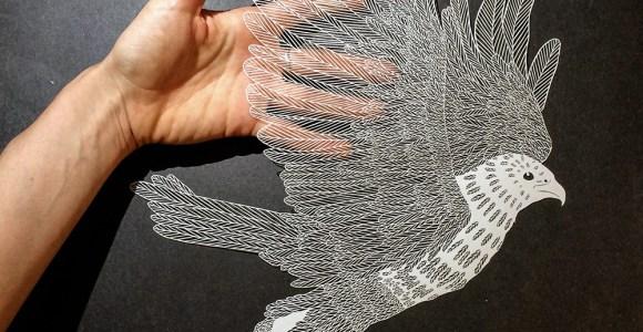 Artista corta meticulosamente o papel para criar figuras fantásticas
