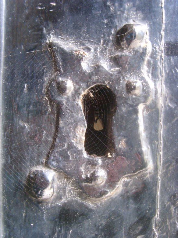 The key hole to the St. Saviour's; always open from the outside - as a spider makes it's home across the olde escutcheon.