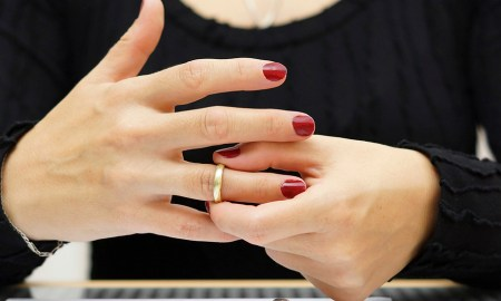 break up . Woman is taking off the ring from hand