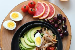 Plate with egg, avocado, chicken. cherry tomatoes and grapefruit slices.