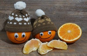 Happy oranges with smiling faces are wearing winter hats. They are looking at orange slices.
