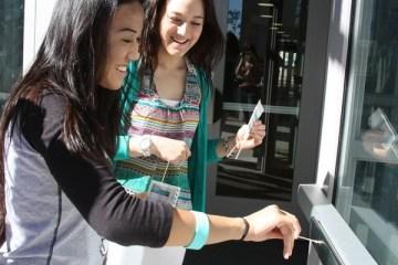 Juniors Merycon Baptista and Tiffany Lewis swab the door handle of the C building. Photo Credit: Bree Eure