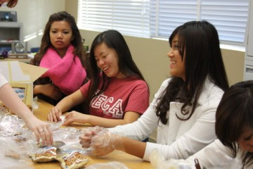 Seniors Marianne Torio, Vivian Sam and sophomore Valerie Cana fill up bags with Famous Amos cookies for Wednesday's spirit activity.Photo Credit: Allison Ho