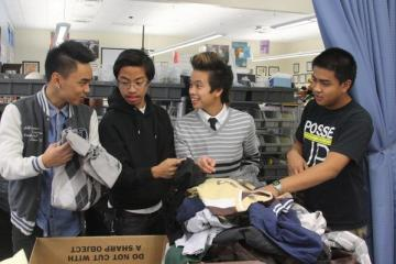 Sophomores, Tristan Correa, JC Diaz, Bryan Aromin, and John Paleracio sort coats for the Salvation Army drive.Photo Credit: Bree Eure