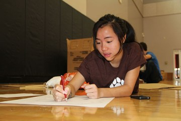"""In order to properly draw her sketch work, sophomore Xueying Zheng lies down in the gym with her other teammates. She represented her major by producing an organ themed arcade game. """"I had an amazing group and this PBL was the most fun. Although, our project broke frequently and we had to fix it, we won!,"""" Zheng said. Photo Credit: Tamara Navarro"""