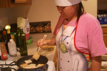 """Junior Cindy Tran cuts onions to put into her dinner. Tran prepared a meal for her family that was Asian influenced. """"I cook for my friends and family when I have time, they really criticize my food, and tell me if it is good or not,"""" said Tran.  Photo Credit: Helen Abraha"""