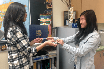 "Sophomores Samantha-Juliane Lam and Maggie Lee exchange a dollar and a star for the Make a Wish foundation. They are both participating in the ""Walk for a Wish"" event, which will take place on April 26. ""I like knowing the fact that I can help someones wish come true just by walking and donating my money and time,"" Lam said.  Photo Credit: Jen Chiang"