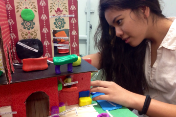 """Sophomore Karen Velayo shows off one of the Spanish homes. Describing each item, she also commented on how long it took each group to finish their house. """"My fingers were so tired of creating furniture,"""" Velayo said """"But I feel maybe i'm a better artist now.""""  Photo Credit: Saramei Kalaoram"""