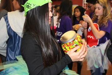 """Senior Kathleen Jaictin participates in the lunch games by playing tic-tac-toe and guessing how many skittles are in the jar. Along with those activities, trivia questions were also asked about the opposite sex for additional points. """"The games weren't easy, but we answered trivia questions correctly and earned some points for the girls,"""" Jaictin said Photo Credit: Mika Pagado"""